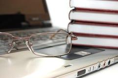 Brillen und Bücher auf Laptop Stockfotografie