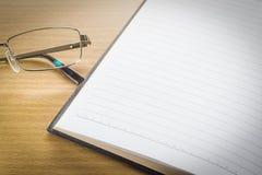 Brillen und offenes Anmerkungsbuch mit Leerseite Stockfoto