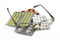 Brillen und Pillen lokalisiert auf weißem Hintergrund Lizenzfreies Stockbild