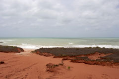 Brilliant  ancient red  rock formations at James Price Point, Broome, North Western Australia on a cloudy summer day. Most of the  oldest beds of red Stock Image
