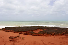 Brilliant  ancient red  rock formations at James Price Point, Broome, North Western Australia on a cloudy summer day. Most of the  oldest beds of red Royalty Free Stock Photo