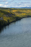 Brilliant autumn colors line the powerful Liard River Stock Image