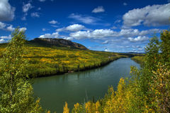 Brilliant autumn colors line the powerful Liard River Stock Photography