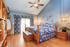 Brilliant bedroom with blue interior and hardwood floor. Royalty Free Stock Photo