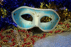 Brilliant blue carnival mask close up on shiny background with festive colored garlands Royalty Free Stock Photos