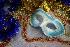 Brilliant blue carnival mask close up on shiny background with festive colored garlands Stock Images