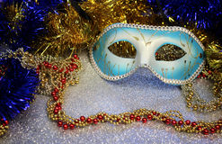 Brilliant blue carnival mask close up on shiny background with festive colored garlands Royalty Free Stock Photography
