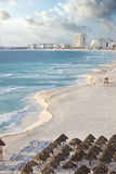 Brilliant blue sea and curving beach in Cancun, Mexico. View along a curving beach of the brilliant blue ocean and distant hotels in Cancun, Mexico royalty free stock photo