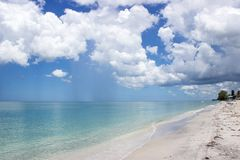 Brilliant Blue Sky and Cumulus Clouds over Empty Beach Royalty Free Stock Photography