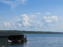 Brilliant blue sky, fluffy white clouds and a lake. Scenic views of Skaneateles Lake in New York State, with a lovely bright blue sky and blue water. Could make royalty free stock image