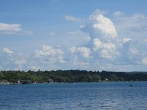 Brilliant blue sky, fluffy white clouds and a lake. Scenic views of Skaneateles Lake in New York State, with a lovely bright blue sky and blue water. Could make stock images
