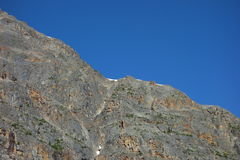 A brilliant blue sky in the mountains. A rock-face in the mountains on a beautiful sunny day royalty free stock image