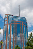 Brilliant Blue Sky Reflected in Glass Office Tower. A red brick and blue glass office tower reflecting blue sky stock image