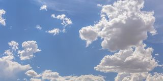 Brilliant blue sky with white puffy clouds. Beautiful view of brilliant blue sky on a sunny day. The sky has white puffy cumulus clouds illuminated by sunlight royalty free stock photos