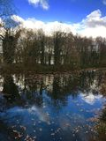 Brilliant blue true lined reflection, clouds and trees reflected in canal Stock Images