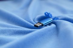 Brilliant blue usb flash memory card with a blue bow lies on a blanket of soft and furry light blue fleece fabric with a lot of re. Lief folds. Memory storage Stock Photos