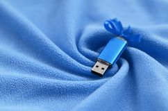 Brilliant blue usb flash memory card with a blue bow lies on a blanket of soft and furry light blue fleece fabric with a lot of re. Lief folds. Memory storage Stock Images