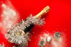 Brilliant Christmas decor.Decorative silver balls and Bottle champagne decorated in festive theme on red background,close-up stock images