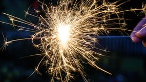 Brilliant closeup of person holding sparkler at night. Beautiful macro closeup of a person holding a sparkler at night Stock Photo