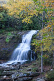 Brilliant fall foliage surrounds soft flowing waterfall Royalty Free Stock Photo