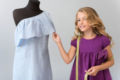 Brilliant girl taking waist measurement. Look at it. Brilliant little girl with a measure tape on the shoulder touching a dress on a mannequin and looking at the Royalty Free Stock Photo