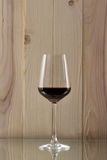 Brilliant glass with red wine on a wooden background on a glass stand. Brilliant glass with red wine on a glass stand Stock Photo