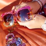 Brilliant glasses in women`s hands. Close-up.  Royalty Free Stock Photography