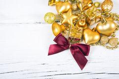 Brilliant gold baubles and cones like christmas decoration. Yellow balls ribbon, gift, red bow and tinsel isolated on white wooden background Royalty Free Stock Images