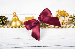 Brilliant gold baubles and cones like christmas decoration. Yellow balls ribbon, gift, red bow and tinsel  on white background Stock Photos