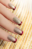 Brilliant Golden manicure. Brilliant Golden manicure with red lacquer on the end of the nail Stock Photos