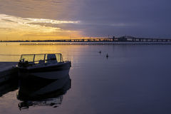 Brilliant golden and violet sunrise over calm waters, recreation Royalty Free Stock Photos