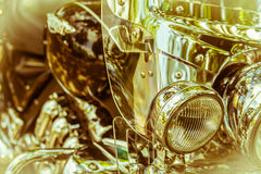 Brilliant headlight motorcycle on a blurry golden background Stock Photography