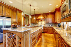 Brilliant kitchen with stained wood cabinets and hardwood floor. Stock Photos