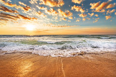 Brilliant ocean beach sunrise. Brilliant ocean and beach lit by sunrise Royalty Free Stock Photo