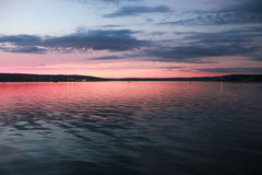 Brilliant Pink Sunset on the Water. A beautiful vibrant pink and red sunset on Niantic Bay, Niantic River, Niantic CT. Dark blue clouds decorate the sky, while royalty free stock photo