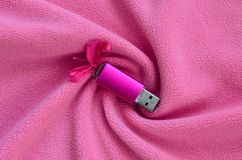 Brilliant pink usb flash memory card with a pink bow lies on a blanket of soft and furry light pink fleece fabric with a lot of r. Elief folds. Memory storage Stock Image