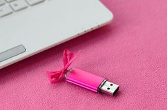 Brilliant pink usb flash memory card with a pink bow lies on a blanket of soft and furry light pink fleece fabric beside to a whi. Te laptop. Classic female gift Royalty Free Stock Image