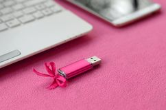 Brilliant pink usb flash memory card with a pink bow lies on a blanket of soft and furry light pink fleece fabric beside to a whi. Te laptop and smartphone Royalty Free Stock Photography