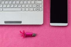 Brilliant pink usb flash memory card with a pink bow lies on a blanket of soft and furry light pink fleece fabric beside to a whi. Te laptop and smartphone Stock Photos
