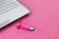 Brilliant pink usb flash memory card with a pink bow lies on a blanket of soft and furry light pink fleece fabric beside to a whi. Te laptop. Classic female gift Stock Photography