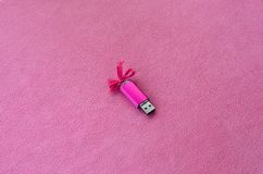 Brilliant pink usb flash memory card with a pink bow lies on a blanket of soft and furry light pink fleece fabric. Classic female. Gift design for a memory card Royalty Free Stock Photo