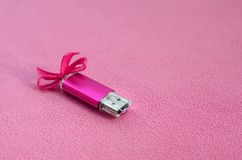 Brilliant pink usb flash memory card with a pink bow lies on a blanket of soft and furry light pink fleece fabric. Classic female. Gift design for a memory card Stock Photo