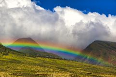 Brilliant rainbow over the lush West Maui mountains. Rainbow over the West Maui mountains with puffy white clouds and brillblue skys stock image