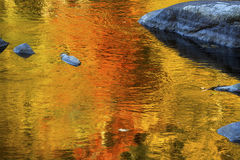 Brilliant reflections of vibrant colors in fall foliage, Canton, Connecticut. Brilliant palette of fall foliage reflections among boulders in the waters of the stock image