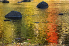 Brilliant reflections of vibrant colors in fall foliage, Canton, Connecticut. Brilliant palette of fall foliage reflections among boulders in the waters of the royalty free stock photography