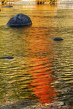 Brilliant reflections of vibrant colors in fall foliage, Canton, Connecticut. Brilliant palette of fall foliage reflections among boulders in the waters of the stock photography