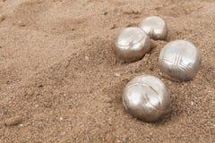 Brilliant silver balls for a bocha on the sand stock photos