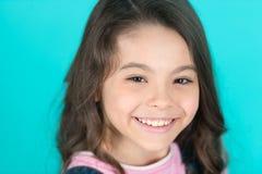 Brilliant smile. Kid happy carefree enjoy childhood. Child charming brilliant smile turquoise background. Kid girl long royalty free stock photos