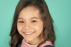 Brilliant smile. Kid happy carefree enjoy childhood. Child charming brilliant smile turquoise background. Kid girl long royalty free stock photo