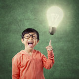 Brilliant student pointing at bright light bulb Royalty Free Stock Image